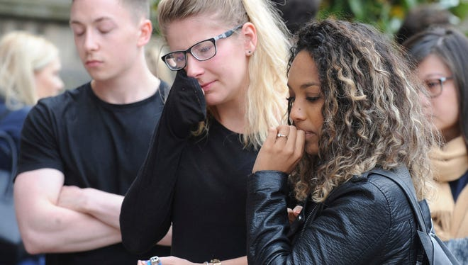 Members of the public react at flower tributes at Albert square in central Manchester, England Wednesday.