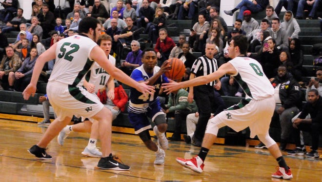 Pascack Valley's defense trys to stop Teaneck's Ja'Quaye James.  Reigning state Group 3 champ Teaneck opened its boys varsity basketball season at Pascack Valley on Friday, December 16.