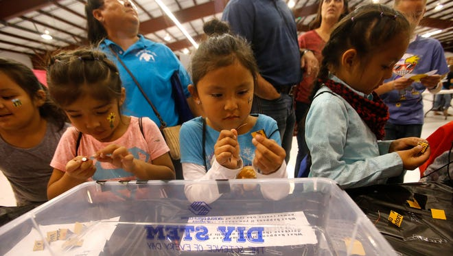 Shalylah Paul, center, and her classmates from Dream Diné Charter School work on an electromagnet Friday during the Discovery Festival at the McGee Park Convention Center.