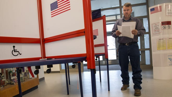 Voter Walter Eaton completes his school board election ballot Feb. 7 at Judy Nelson Elementary School in Kirtland. A local state lawmaker is proposing that all local elections be consolidated and held on the same day.