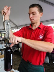 Brian Moore of Cove Point Winery opens a bottle of wine at the Salisbury Autumn Wine Festival on Saturday afternoon in Permbeton Park.
