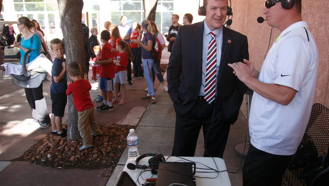 """Dixie State University president Richard """"Biff"""" Williams chats with radio talk show host Devin Dixon as people wait in line for entry to the university's reveal of their new nickname and mascot Monday, April 11, 2016 on the campus of Dixie State University."""