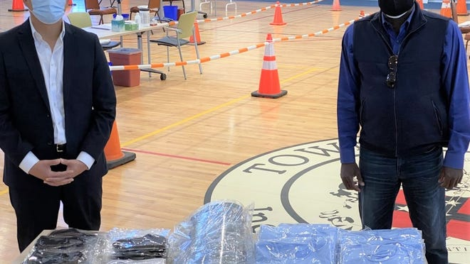 Quincy Asian Resources, Inc. (QARI) President and CEO Phillip Chong (left) stands next to some of the  $5,000 worth of Personal Protective Equipment (PPE) his company donated for Randolph residents, secured by Randolph town councilor Ken Clifton.
