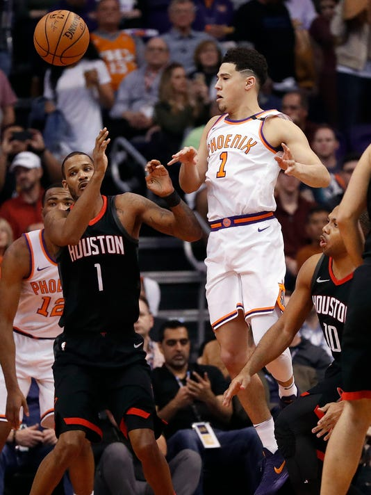 Phoenix Suns guard Devin Booker passes the ball past Houston Rockets forward Trevor Ariza,front  left, during the first half of an NBA basketball game Friday, Jan. 12, 2018, in Phoenix. (AP Photo/Matt York)
