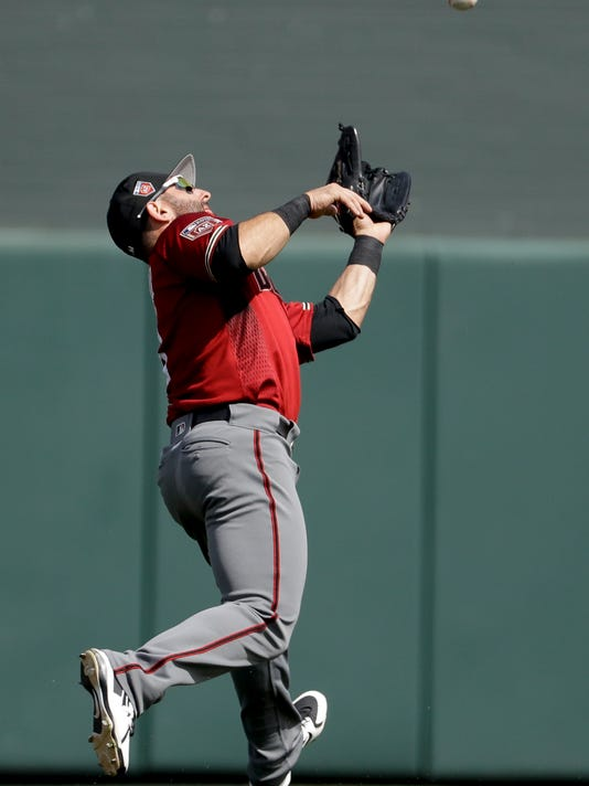 Arizona Diamondbacks left fielder Daniel Descalso catches a fly ball hit by Colorado Rockies' Charlie Blackmon during the third inning of a spring baseball game in Scottsdale, Ariz., Sunday, March 25, 2018. (AP Photo/Chris Carlson)