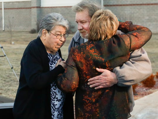 Marsha Iler, right, and Freda Jennings hug Brad Jennings