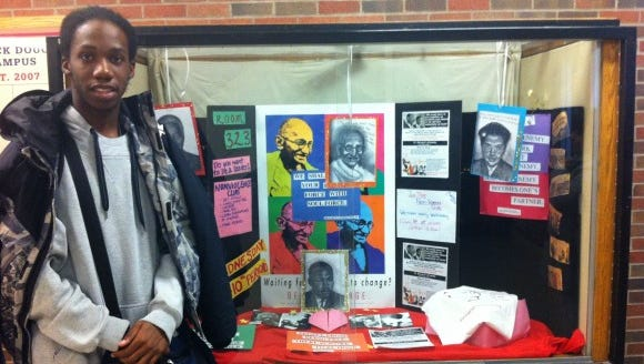 Dennis Smith in front of Non-Violent Club display case at Douglass.