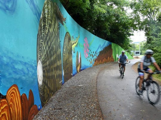 Bicyclists ride past a new 230-foot mural Wednesday, July 6, 2016, on the Third Creek Greenway. The mural, which depicts freshwater mussels, was spearheaded by the Center for Biological Diversity as part of a nationwide project to use art in public places to increase appreciation for regional biodiversity. (MICHAEL PATRICK/NEWS SENTINEL)