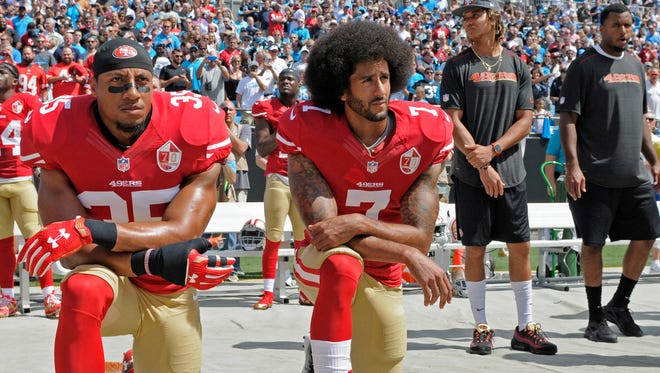 Colin Kaepernick and Eric Reid kneel during the national anthem prior to Sunday's game.