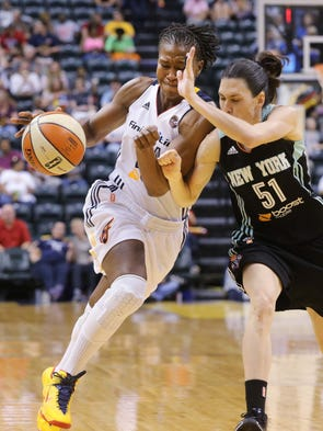 Tamika Catchings drives on NY defender Anna Cruz in the second half. The Indiana Fever hosted the New York Liberty in WNBA action in Indianapolis Thursday August 14, 2014.