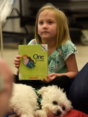 "Gracie Kennedy, 6, shows off the book she read to ""Buster"" Saturday, March 17, 2018 during the Pet Partners:Read With Me session at the Tryon Branch Library. Pet Partners:Read With Me is a special initiative to promote literacy and instill a lifelong love of reading by having children read to therapy animals."