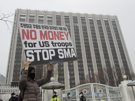 In this March 5, 2019, photo, a protester holds a banner against SMA, or Special Measures Agreement, during a rally in front of a government complex in downtown Seoul, South Korea. South Korea and the United States on March 9, 2019, signed a deal that would increase Seoul's financial contribution for the deployment of U.S. troops in the Asian country.