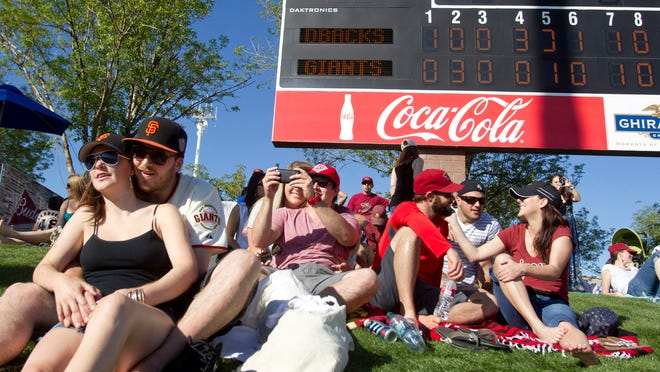 Giants fans Philip Atkinson and Lily Wellstein of San Francisco watch a game at Scottsdale Stadium.