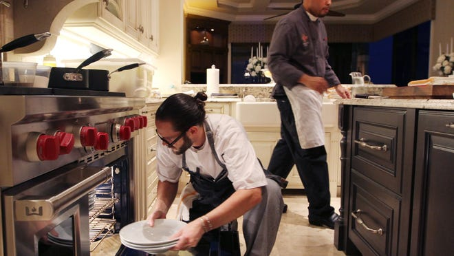 Chef Joe Pittman, of Mereday's Fine Dining Restaurant in Naples, puts plates in the oven to warm them in preparation for the vintner dinner at the Tolers home in Bonita Springs on Friday night.