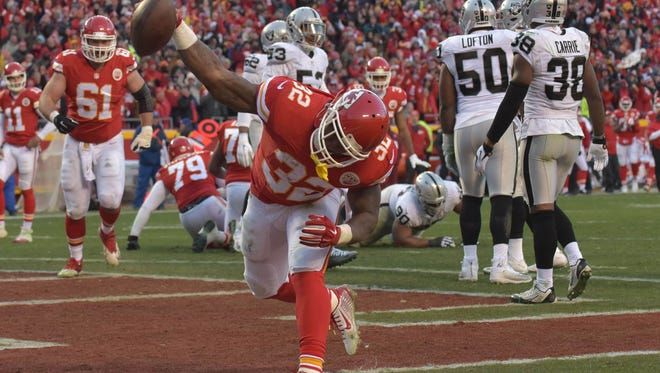 Kansas City Chiefs running back Spencer Ware (32) spikes the football after scoring during the first half against the Oakland Raiders at Arrowhead Stadium.