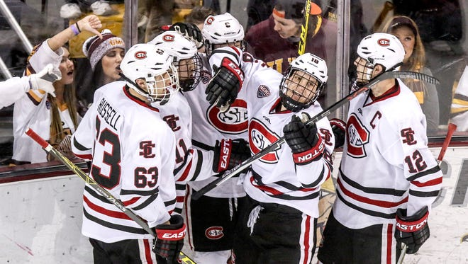 Patrick Russell, Kalle Kossila, Joey Benik, Judd Peterson and Ethan Prow celebrate after Kossila scored a goal in the second period Friday against Minnesota-Duluth at AMSOIL Arena in Duluth.