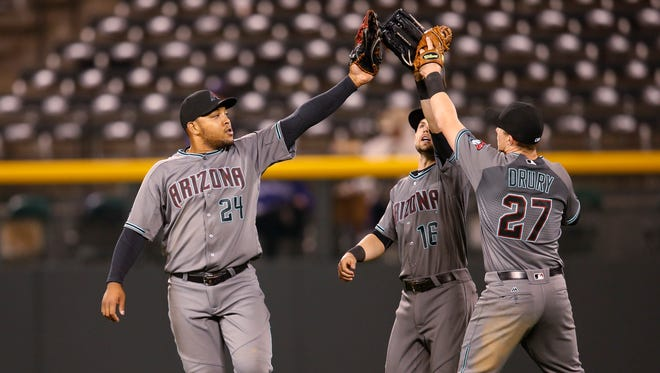 Arizona Diamondbacks left fielder Yasmany Tomas, left, celebrates with center fielder Chris Owings and right fielder Brandon Drury after the Diamondbacks defeated the Colorado Rockies 5-1 in a baseball game Tuesday, May 10, 2016, in Denver.
