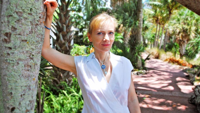 North Naples artist Veronica winters wears one of her new Seascape Necklaces. She began suspending found seashells in resin to commemorate her trips to the beach. She sells the keepsakes on Etsy.