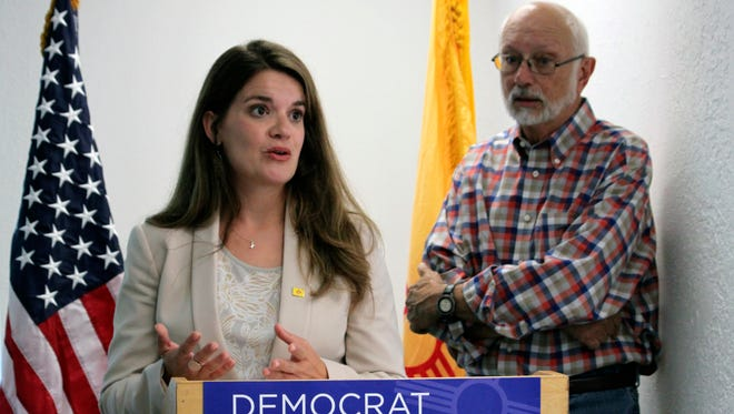 Democratic candidate for secretary of state Maggie Toulouse Oliver, left, and Sen. Gerald Ortiz y Pino discuss discrepancies uncovered in campaign finance records during a news conference in Albuquerque, N.M., Wednesday, Aug. 10, 2016. Toulouse Oliver says inconsistencies between online and printed records appears to be a glitch that has gone unnoticed for years.