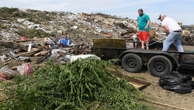Garrett Eblen (left) and Jason Daugherty unload a trailer of debris at the Henderson County construction demolition and debris landfill off of Wolf Hills Road Tuesday. The CD&D landfill has about four years left before it reaches its fill level, August 23, 2016.