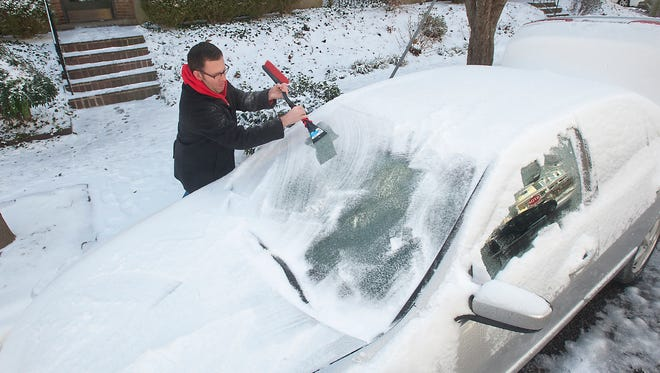 Jason Ostrander chips away at the ice on his car's windshield in Cherokee Triangle. Jan. 13, 2018