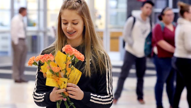 Mandi Andrews takes a bunch of orange carnations out for delivery to Greenfield High School classrooms on Wednesday. Students sold orange carnations before the start of classes. Proceeds will be sent to the victims of the Parkland, Fla., school shooting.