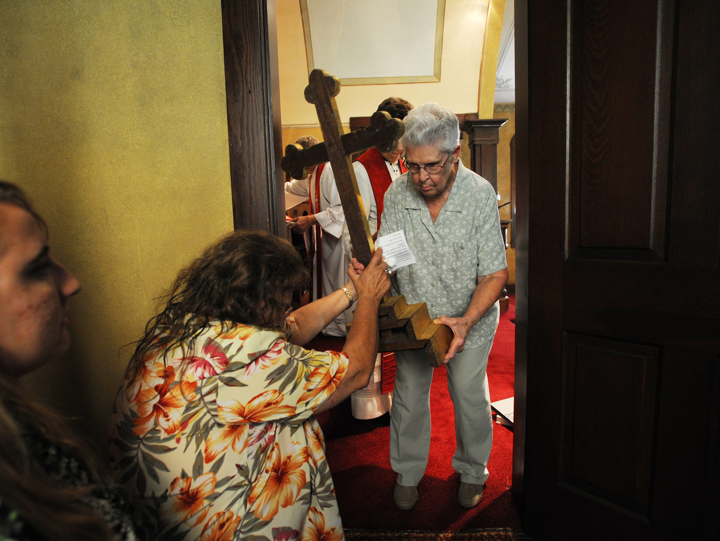 Willajene Vensel removes the cross from the chancel