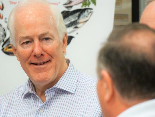 U.S. Sen. John Cornyn speaks with several business