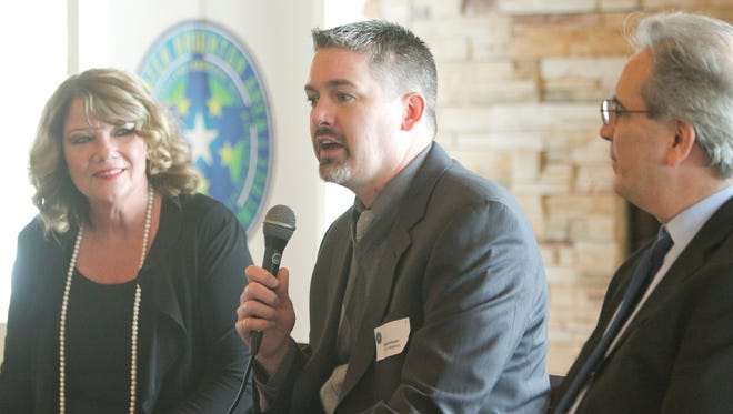Brighton city manager Nate Geinzer speaks in a luncheon of the Greater Brighton Area Chamber of Commerce held at Oak Pointe Country Club, along with county administrator Ken Hinton, right, and moderated by chamber president Pam McConeghy.