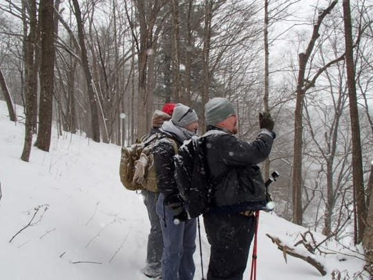 A group of veterans takes a break from snowshoeing at an outdoor event organized by Iowa mountaineers John and Andy Anderson at Backbone State Park.