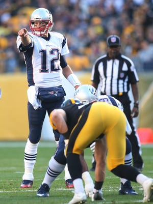 New England Patriots quarterback Tom Brady (12) gestures at the line of scrimmage against the Pittsburgh Steelers during the first quarter at Heinz Field.