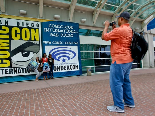 Early arrivals among fans take photos of themselves outside the convention center during preparations for the 2015 Comic-Con International Tuesday, July 7, 2015, in San Diego. The event features the hottest films, TV shows and video games and runs July 9-12, 2015.  (AP Photo/Lenny Ignelzi)