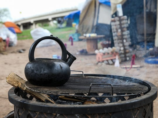 Water warms in kettle in the tent city under Houston Harte Expressway.