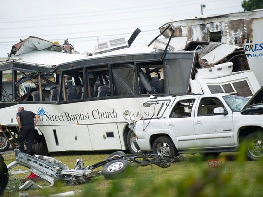 Investigators examine the church bus involved in the fatal Interstate 40 accident on Thursday, Oct. 2, 2013, at a Tennessee Department of Transportation facility in Newport. Authorities suspect a blown tire caused the bus  to cross the median and crash into an SUV and tractor-trailer, killing eight people and injuring 14.  (Paul Efird/News Sentinel)