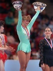 Tonya Harding raises her trophies after winning the