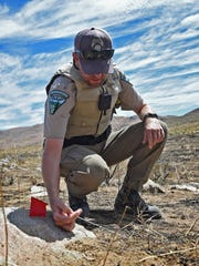 Scott Fischer, a BLM fire investigator, points out clues that he looks for while investigating a brush fire.  He stands in an area in Golden Valley where a brush fire was started by recreational target shooters. The people involved attempted to put the fire out but where unable to and called 911.
