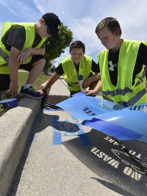 """Luke Walentowski, from left, Jack Konop and Will Verhagen unveiled results after using blue spray paint to stencil """"Dump No Waste; Drains To Lake'' next to a drain sewer near the waterfront along Pennsylvania Street in Sturgeon Bay on June 21, 2018. Hosted by the Door County Soil and Water Conservation Department, the members Boys & Girls Club of Door County learned about stormwater run off. Tina M. Gohr/USA TODAY NETWORK-Wisconsin"""