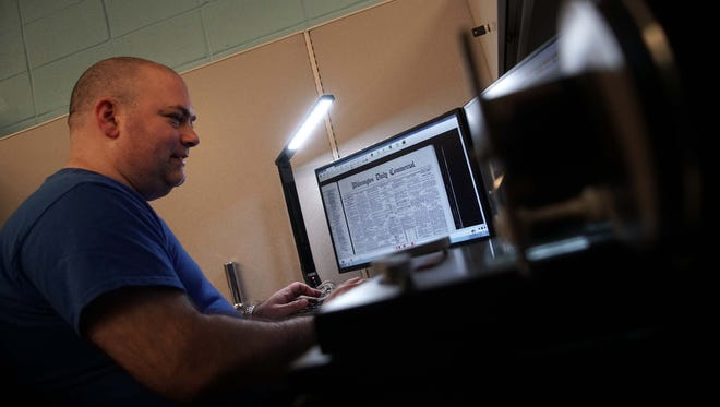 David Cardillo, a library assistant at the University of Delaware, prepares microfilm containing old newspapers from around Delaware to be sent out for digitizing.