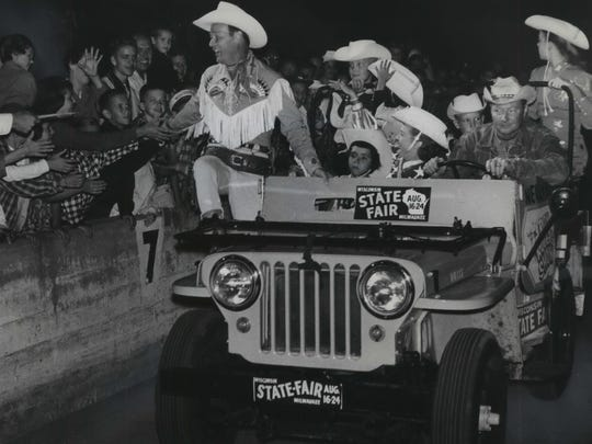 Fans greet television star Roy Rogers and his troupe at the opening night of his Wisconsin State Fair grandstand show on Aug. 15, 1958. That's comedian/sidekick Pat Brady driving the car. This photo was published in the Aug. 16, 1958, Milwaukee Journal.