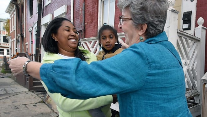 Angela Anderson, right, hugs Gervana Crick, holding Gervian Crick, age 4, after asking if she needed anything on Oct. 31, 2016, since fires damaged homes on East Maple Street in York over the weekend.