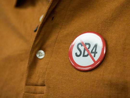 A resident wears a anti-SB4 pin  during Nueces County Commissioners Court meeting on Wednesday, Aug. 9, 2017.