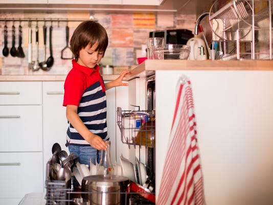 Preschool child, boy, helping mom, putting dirty dishes in dishwasher at home, modern kitchen