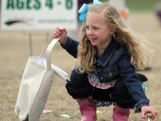 A young girl picks up a peiece of candy at the Portland Easter Egg Hunt on Sun. March 25, 2018.