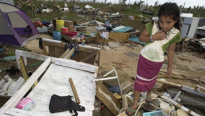 In this Dec. 12, 2002 file photo, Alverlyn Nimeisa walks around the wreckage of her Dededo home following Supertyphoon Pongsona.