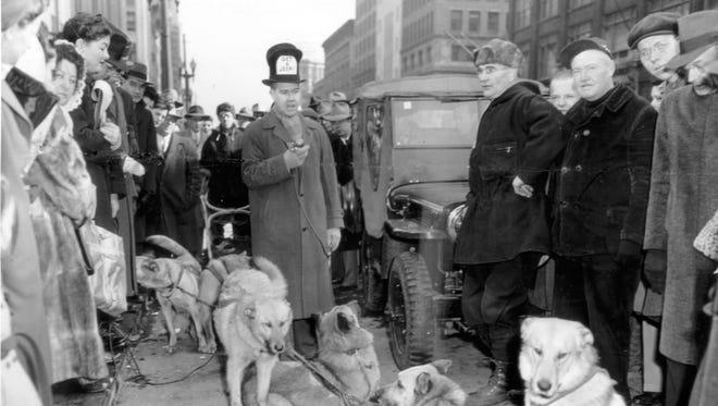 1951 photo of Jim Shelton  interviewing Alaskan dog sledders passing through Indianapolis.