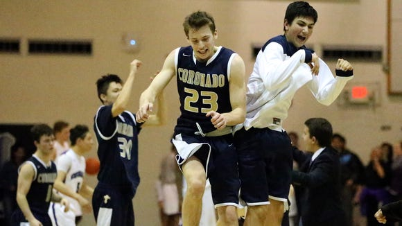 The Coronado boys basketball team celebrates after beating West Side rival Franklin 41-36 in overtime Friday night at Franklin.