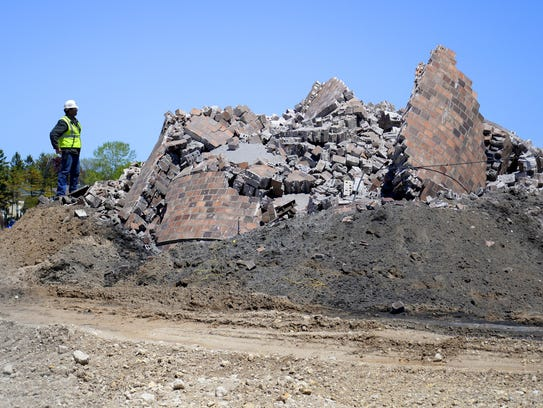 A demolition crew member inspects the base of what
