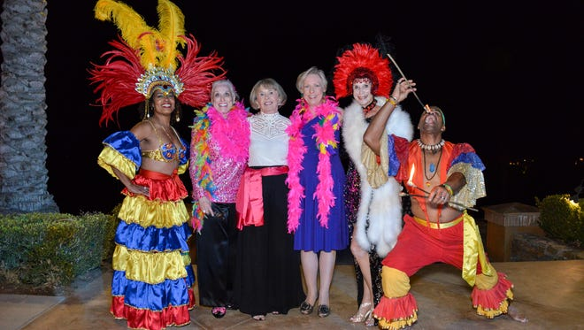 RIO Dancer, Event Chair Sandy Woodson, President of the Muses and Patroness Circle Linda Weakley, Marge Dodge, Terri Neuman, and RIO Fire Eater.