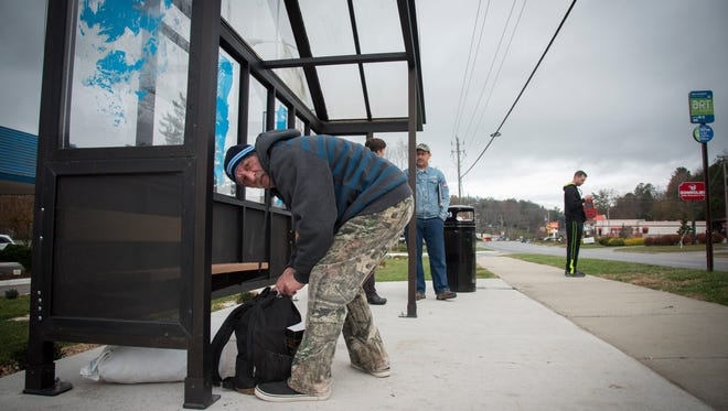 William Harmon, a homeless veteran who walked from the VA Medical Center, waits for the bus in the new bus shelter at Veterans Restoration Quarters recently.