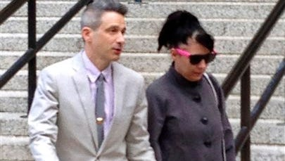 """Beastie Boys rapper Adam """"Ad-Rock"""" Horovitz leaves federal court in Manhattan with his wife Kathleen Hanna after testifying at a copyright trial stemming from a lawsuit his musical group brought against a beverage maker over the use of five of its songs in a video in New York."""